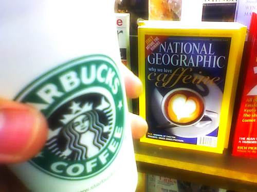Holding a Cup of Starbucks Coffee in a Book Shop