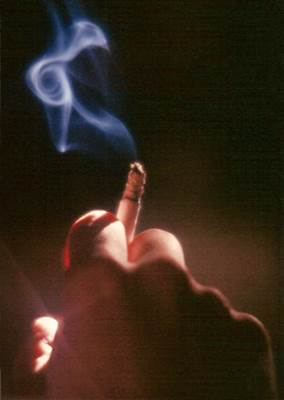 A Lit Cigarette in a Smoker's Hand and Spiralling Smoke