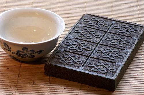 A Box of Brick Tea (Tuo Cha) and an Empty Tea Bowl