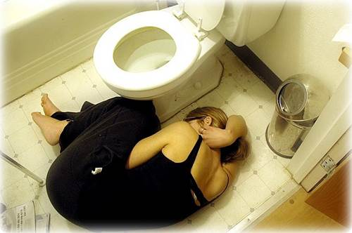 Girl with Stomach Pain Lying Curled Up on Bathroom Floor