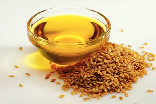 Flaxseed Oil in a Small Glass Bowl and a Handful of Flaxseeds