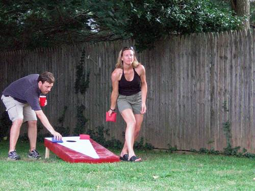 A Couple Playing a Game of 'Cornhole' in a Family Backyard