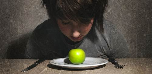 Young Boy Reluctant to Eat an Apple on a Plate