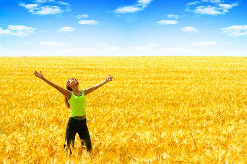 Back Pain-Free Girl with Outstretched Arms in a Wheat Field