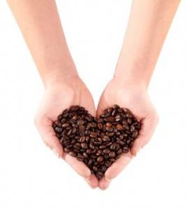 Coffee Beans Held in a Heart Shape in Two Hands