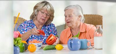 Woman Offering Fresh Vegetables to her Elderly Mother