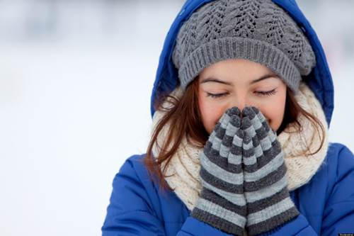 Girl Bundled Up to Prevent Windburn Covering Her Face with Gloved Hands