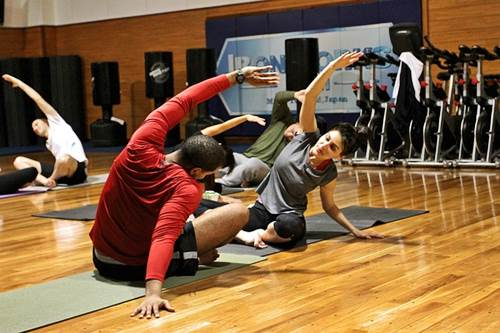 People Doing Stretch Exercises in a Gym